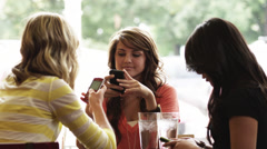 MS Three young women using mobile phones in cafe, waiter serving plate, Provo, Stock Footage