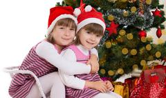 Sisters hugging in sledge under Christmas tree - stock photo