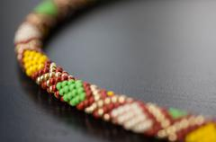 knitted necklace from beads with a geometrical pattern close up - stock photo