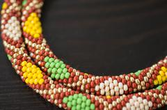 knitted necklace from beads with a geometrical pattern - stock photo
