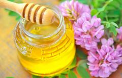 glass jar full of honey and stick with acacia pink and white flo - stock photo