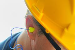 Yellow earplug into the ear Stock Photos
