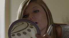 CU Teenage (16-17) girl applying mascara on bed, American Fork, Utah, USA Stock Footage