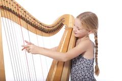 young girl in blue playing harp - stock photo