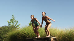 SLO MO WS Two teenage (16-17) girls jumping into swimming pool, American Fork, Stock Footage
