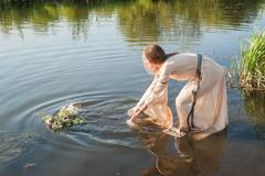 Beautiful girl lowers wreath in water Stock Photos