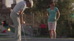 MS Woman sneezing, distracting man preparing to hit golf ball, Orem, Utah, USA Stock Footage