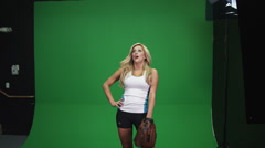 A blonde woman catching a baseball in front of a green screen Stock Footage