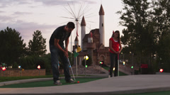 MS Man putting on miniature golfcourse, woman watching standing nearby, Orem, Stock Footage
