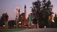 MS Family of five playing on miniature golf course, boy (10-11) making putt into Stock Footage