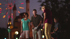 MS Family of five playing on miniature golf course, girl (12-13) making putt Stock Footage