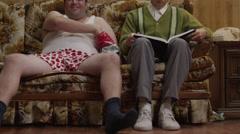 MS Obese man wearing underwear sitting on sofa next to geek reading book Orem, Stock Footage