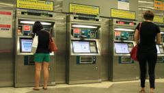 People buying subway tickets at ticket machine Stock Footage