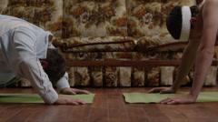 MS TU Two men doing yoga on exercise mats in living room, Orem, Utah, USA Stock Footage