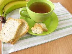 Tea and twice baked crisp bread and banana - stock photo