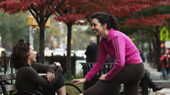 MS Young woman stretching at bench and talking to friend tying shoe, Manhattan, Stock Footage