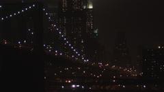 MS TU Brooklyn Bridge illuminated at night, downtown skyline in background, New Stock Footage