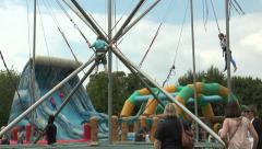 Children on a bunjee trampoline at an English country fair Stock Footage