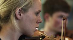 CU Woman playing violin, man in background, Buena Vista, Virginia, USA Stock Footage