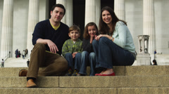 MS Portrait of family with two children (4-5, 6-7) sitting on steps in front of Stock Footage