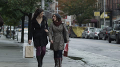 WS CU Two young women with shopping bags walking on street, Manhattan, New York - stock footage