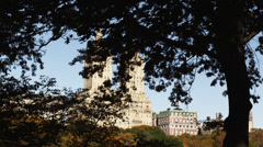 WS PAN View of skyscrapers through Central Park tree branches, New York City, Stock Footage