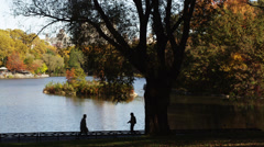 WS PAN HA Silhouettes of people walking by lake in Central Park, New York City, Stock Footage