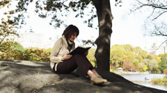 MS PAN Woman reading book resting on man's lap in Central Park, New York City, - stock footage