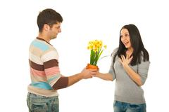 Man offering flowers to amazed woman Stock Photos