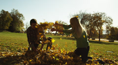 MS SLO MO Young man and young woman throwing leaves in park / Provo, Utah, USA Stock Footage