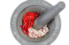 old stone mortar and pestle with red chill and garlici - stock photo
