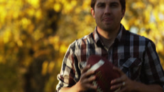 MS TD SLO MO Young couple playing football in park, falling down on grass / Stock Footage