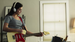 MS PAN Teenage girl (16-17) playing electric guitar in home/ Orem, Utah, USA Stock Footage