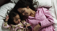 MS HA Mother and daughter (2-3) playing with mobile phone in bed/ Orem, Utah, Stock Footage
