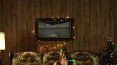 MS TD Lonely young woman with party blower, on sofa at Christmas/ Orem, Utah, Stock Footage