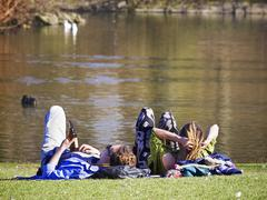 Couple relaxing at waters edge Stock Photos