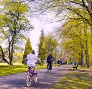 Bike riders in spring park - stock photo