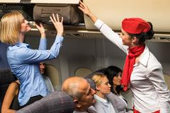 Flight attendant help passenger with luggage cabin - stock photo