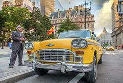 Vintage scene in New York. Old yellow cab in city streets Stock Photos
