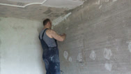 Stock Video Footage of apartment renovation. the man plasters a wall