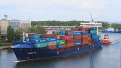 Large container ship is being assisted by a tug to container terminal 2 Stock Footage