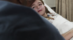 MS Girl (8-9) lying in hospital bed being visited / Payson, Utah, USA Stock Footage
