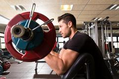 Biceps preacher bench arm curl workout man at gym Stock Photos