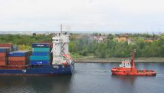 Large container ship is being assisted by a tug to container terminal 5 Stock Footage