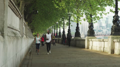 WS Man and woman jogging on riverbank / London, UK Stock Footage