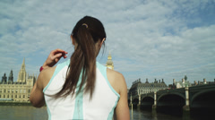 MS Rear view of woman stretching back on riverbank, Westminster Bridge and Stock Footage