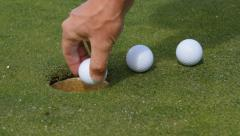 Close-up of golf ball going into the hole Stock Footage