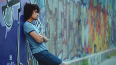 Teenager standing against the wall, which is painted graffiti Stock Footage