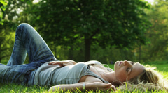WS Woman lying in park listening to music, joined by man / London, UK Stock Footage