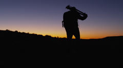 WS PAN Silhouette of photographer walking, carrying tripod in desert at sunset/ Stock Footage